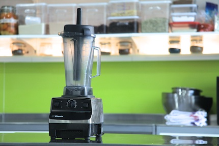 Vitamix on a steel bench with a green background