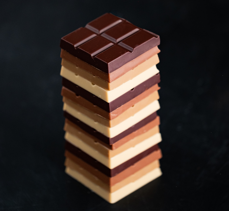 Stack of various types of raw chocolate on a black background