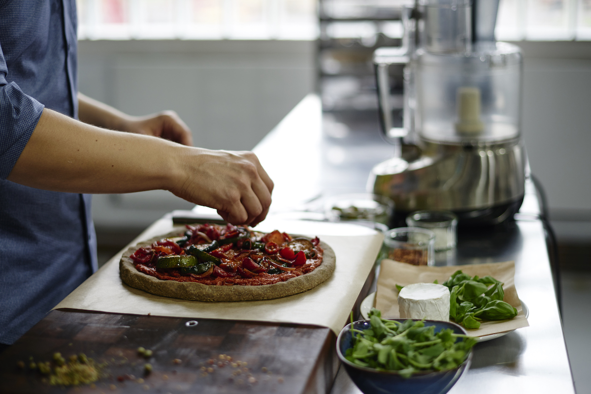 Russell James garnishing a raw pizza on a wooden chopping board