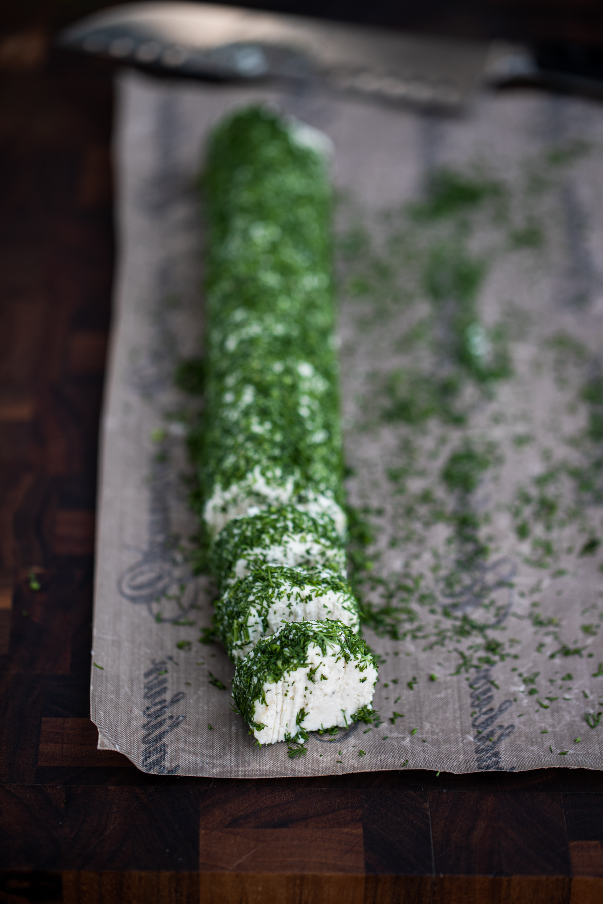 Macadamia cheese log rolled in herbs and cut into rounds on a dehydrator nonstick sheet with a knife in the background