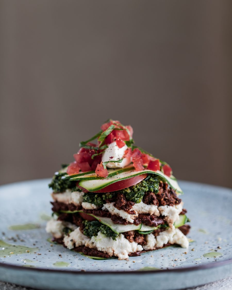 Raw vegan lasagne on a blue plate and white table top