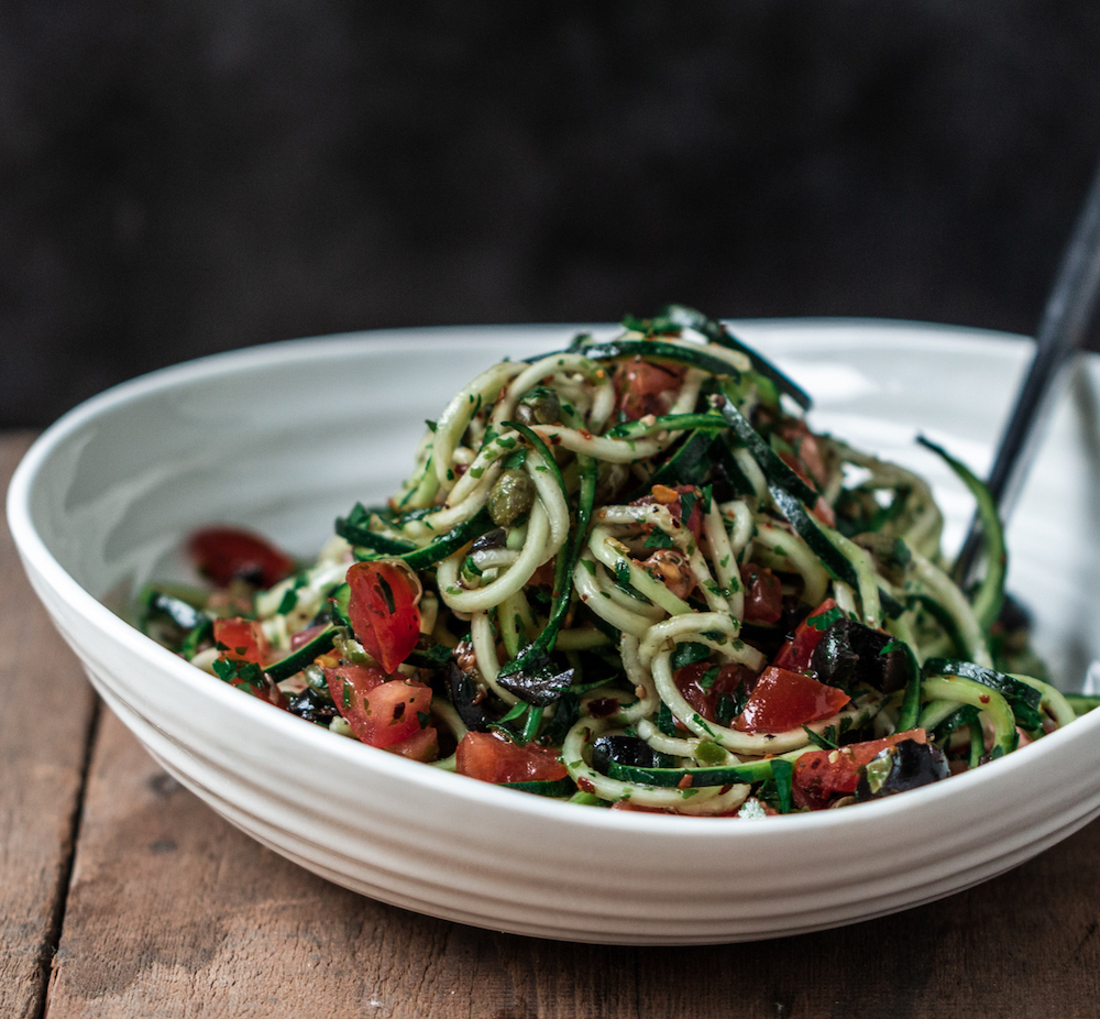 Raw zucchini pasta putanesca in a white bowl on a wooden surface