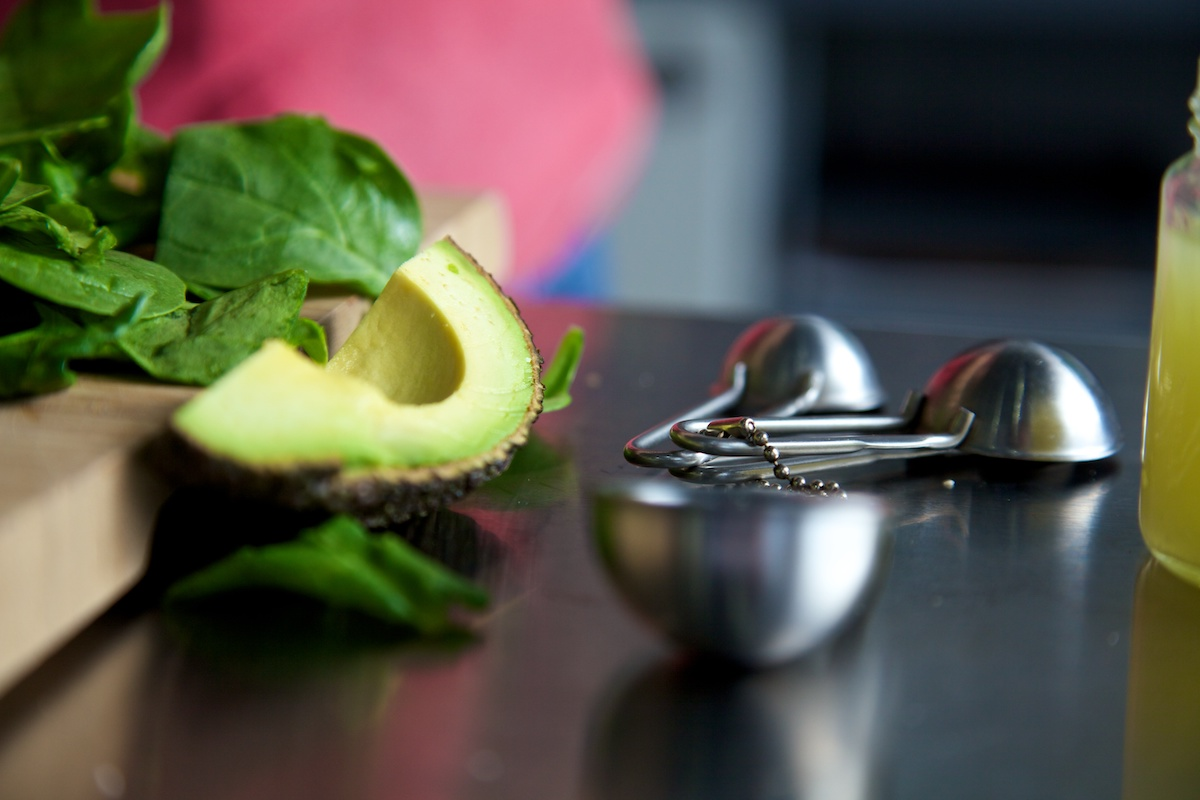 Quarter of an avocado, raw spinach, jar of lemon juice and measuring spoons on a stainless steel surface.