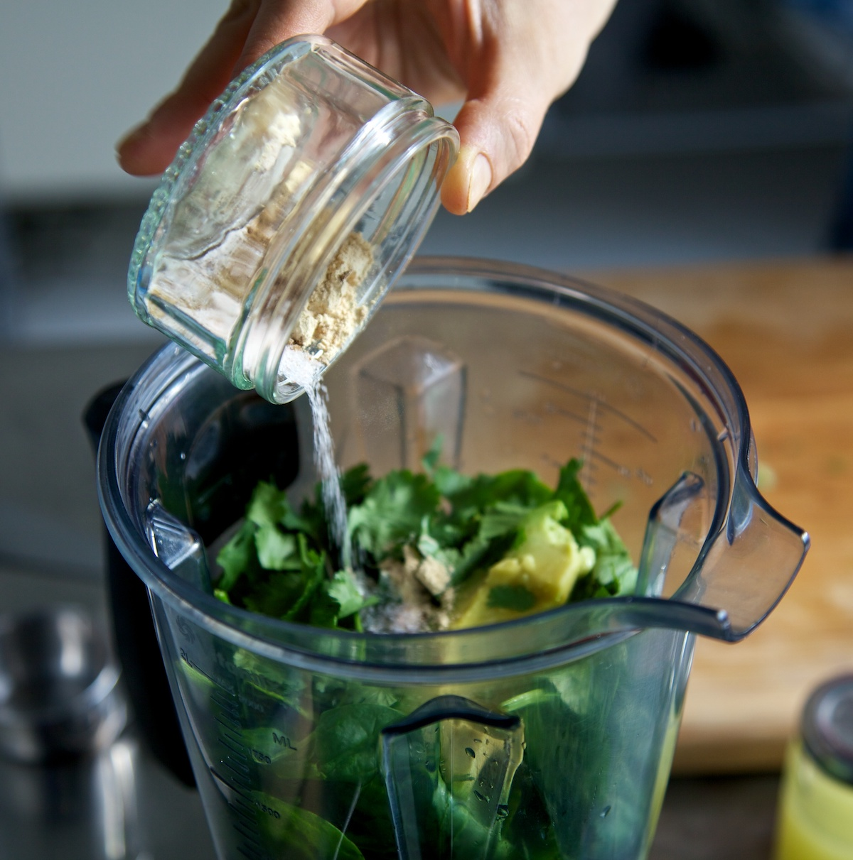 Adding spices to the Vitamix jug with the raw avocado, spinach and lime soup ingredients in