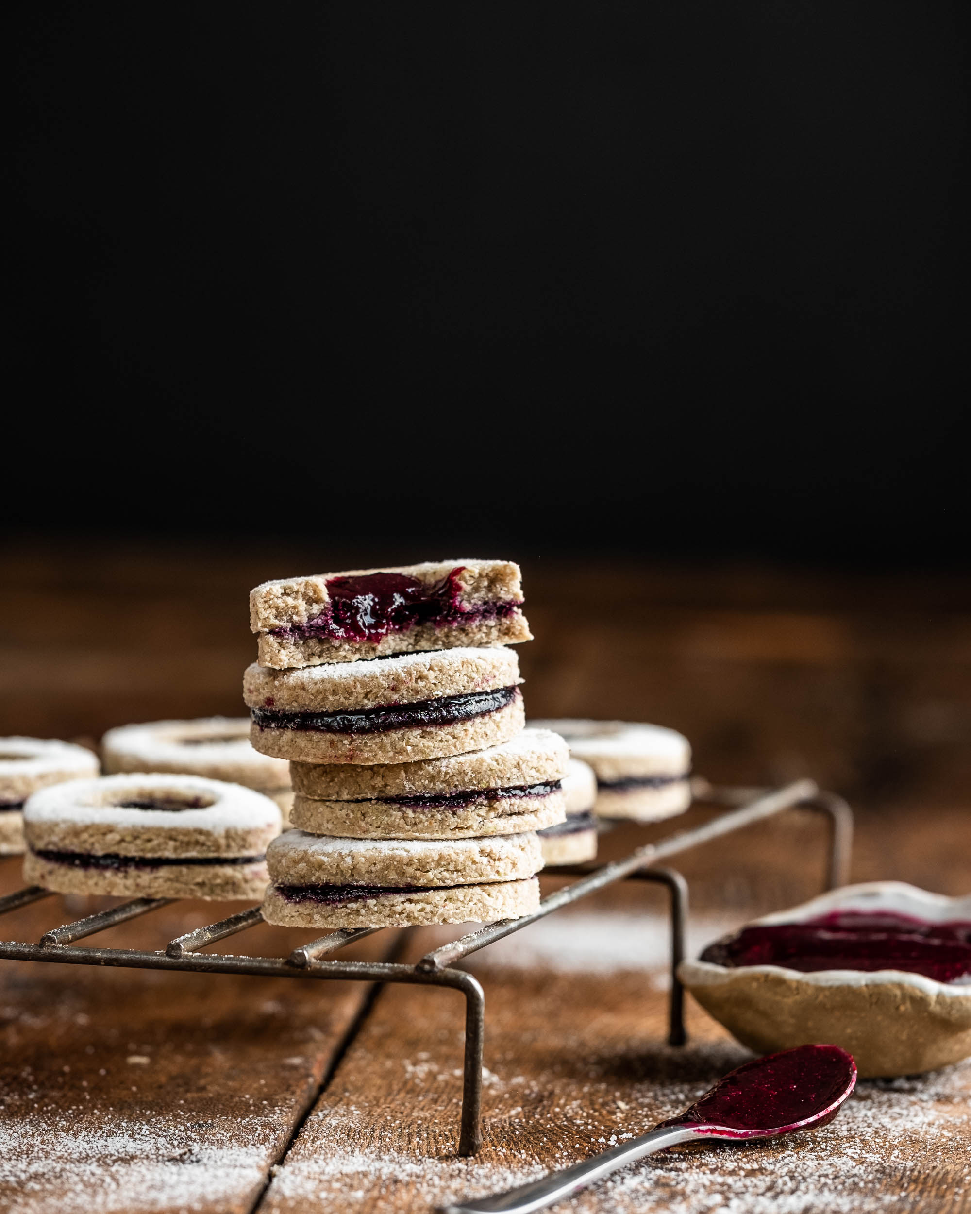 Raw linzer cookies on a wire tray and wooden table