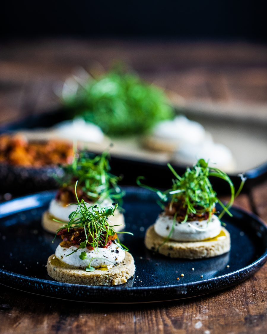 Raw pizza canapes on a black plate and wooden board