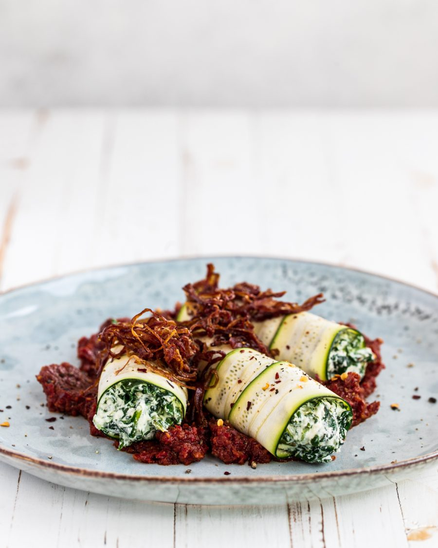 Raw Courgette Cannelloni on a blue plate and white background
