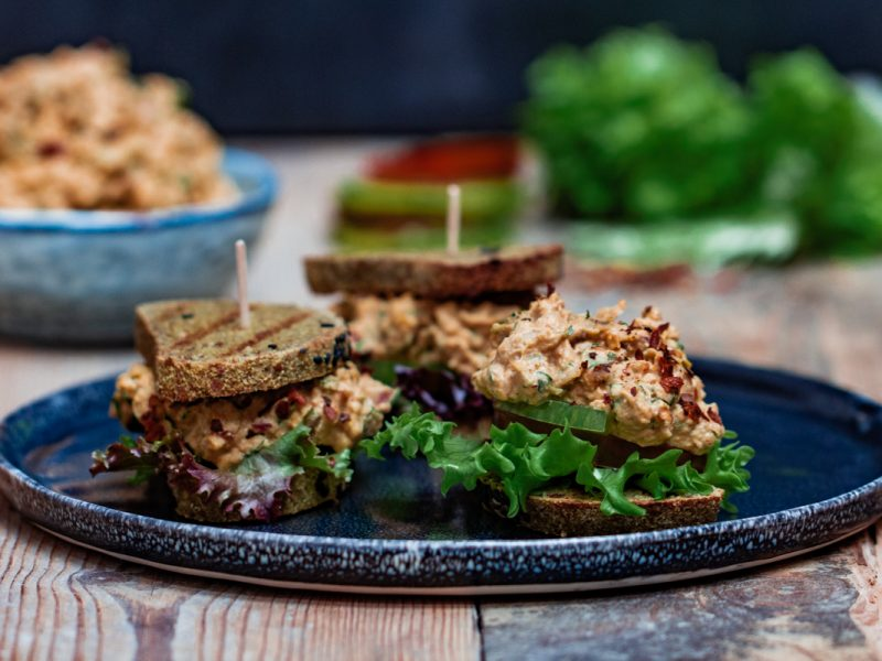 Raw bread sandwiches with coronation chickpea salad stacked up on a wooden table