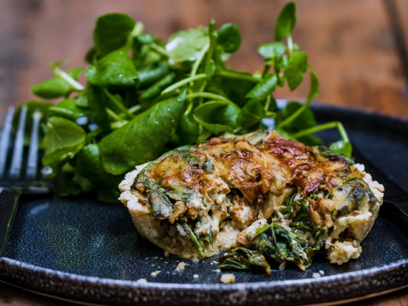raw wild mushroom spinach quiche on a black plate and wooden background